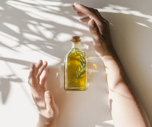 sunlight-falling-hands-covering-oil-bottle-white-background